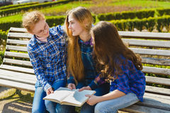 Little pretty schoolgirls reading a book and sitting on bench outdoor Stock Photography