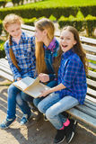 Little pretty schoolgirls reading a book and sitting on bench outdoor Stock Photos