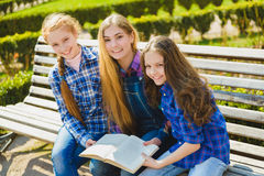 Little pretty schoolgirls reading a book and sitting on bench outdoor Royalty Free Stock Photo