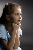 Little pretty thoughtful girl on the arm-chair Stock Photography