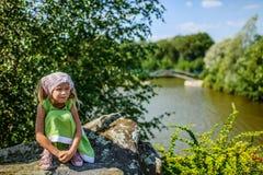 Little pretty thoughtful girl sitting near lake Stock Photo