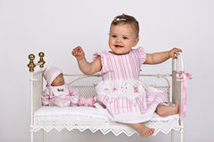Little princess. Little girl sitting in an old bed for dolls Stock Photography