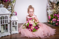 A little princess in a beautiful pink dress sits on the floor near flower stands and lanterns, holds a bouquet of peonies, magnoli stock photography