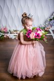 A little princess in a beautiful pink dress sniffs a bouquet of peonies, magnolia, berries and greenery against a white wall and f royalty free stock image