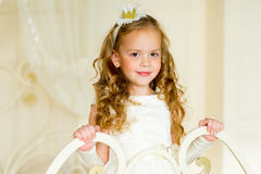 Little princess on the bed. In classic dress and vintage atmosphere of the room royalty free stock photos