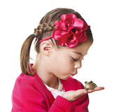 Little Princess kissing a frog. A cute little girl attempting to kiss her pet frog with the hopes of it turning into a prince Royalty Free Stock Photography