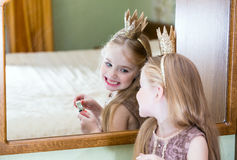 The little princess looks in the mirror.  Royalty Free Stock Images