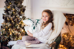 Little princess sit on armchair with deer pillow by Christmas tree at home Royalty Free Stock Image