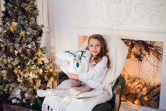 Little princess sit on armchair with deer pillow by Christmas tree at home Stock Image