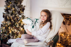Little princess sit on armchair with deer pillow by Christmas tree at home Royalty Free Stock Photography