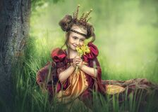 A little Princess sits on the grass.