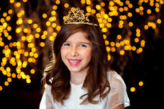 A Little Princess Smiles With a Giggle and a Tiara. A happy little girl sits, looking at the camera with a tiara and sparkle lights behind her.  She seems to be Stock Photography