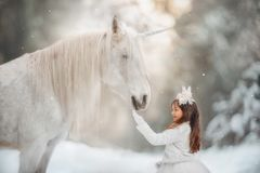 The little princess with an unicorn in the forest. The little girl with a white horse-unicorn in a winter park royalty free stock images