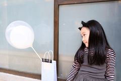 Little princess in gray dress holding baloons. Little princess wearing gray dress and tiara sit by the window holding colorful baloons royalty free stock photography