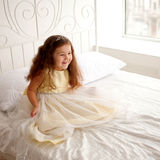 Little princess on a white bed. Royalty Free Stock Photography