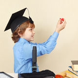 Little professor in academic hat conducts research with microscope Royalty Free Stock Image