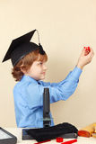 Little professor in academic hat conducts scientific research with microscope Stock Photography