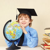 Little professor in academic hat with globe among old books Royalty Free Stock Images