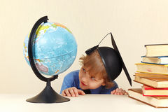 Little professor in academic hat looks at geographical globe Stock Photos