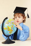 Little professor in academic hat looks at globe Royalty Free Stock Photos
