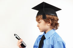 Little professor in academic hat with a magnifying glass on white background Royalty Free Stock Photos