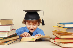 Little professor in academic hat reading old books Stock Photography