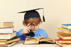 Little professor in academic hat reading an old books with magnifying glass Stock Photo