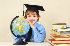 Little professor in academic hat showing on the globe among old books Stock Image