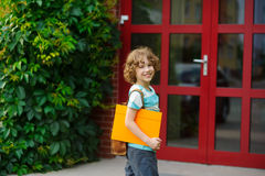 The little pupil on a schoolyard. The school student with a smile looks in the camera. Behind shoulders at the pupil a satchel, in hands the bright folder Stock Image