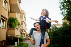 Little pupil sitting on the shoulders of his father. Royalty Free Stock Image