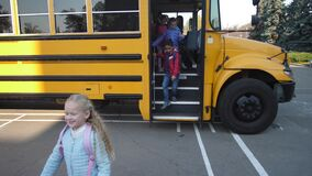 Little pupils getting off bus and going to school