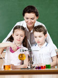 Little pupils pour chemical liquids. In different flasks while studying chemistry with their teacher Stock Images