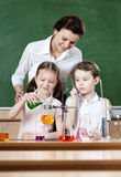 Little pupils study chemical liquids. With their teacher Stock Photo