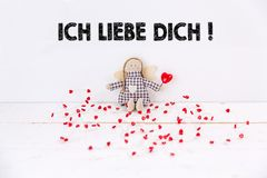 Little puppet with red hearts sitting on white background with `Ich liebe dich` text. Tranlation: `I love you` stock photos