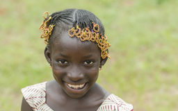 Little pure African girl smiling outdoors. Young african girl with traditional accessories in hair looking at camera Stock Photo