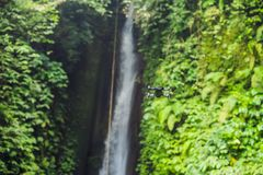 Little quadcopter flying around waterfall Leke Leke Bali island Indonesia.  stock photo