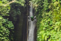 Little quadcopter flying around waterfall Leke Leke Bali island Indonesia.  royalty free stock photography
