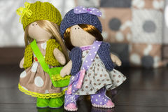 Little rag dolls dressed in polka dot dresses, knitted hats with bows, knitted vests, sneakers. Little rag dolls dressed in polka dot dresses - light brown and stock photos