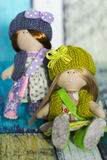 Little rag dolls dressed in polka dot dresses - light brown and blue, - knitted hats with bows, knitted vests, sneakers. And with bags stock photo