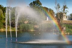 Little rainbow from the water fountain lake, city park pond, water jet beats up against the background of green trees. Summer weekend rest stock photography