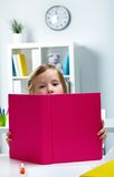 Little reader. Portrait of lovely girl reading big book stock photo