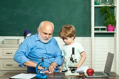 Little ready to study. Father and son. Teachers day. Happy cute clever boy and old tutor with microscope.