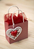Little red bag with a decorative motif of a heart on wood background Royalty Free Stock Photos