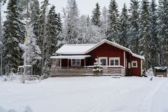 A little red cabin in a forest covered in snow. Standing in Sweden Royalty Free Stock Photos
