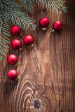 Little red christmas baubles with branches of firtree on old woo Stock Photos
