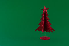 Little red christmas tree on green background. Little, red metallic christmas tree on green background Stock Photos
