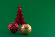 Little red christmas tree with tree adornments on green backgrou. Little, red metallic christmas tree with tree adornments on green background Royalty Free Stock Image