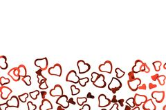 Little red confetti hearts on white background. royalty free stock image