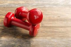Little red dumbbells on the floor stock image
