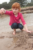Little red haired girl building a sand castle with wet sand at a Stock Photo